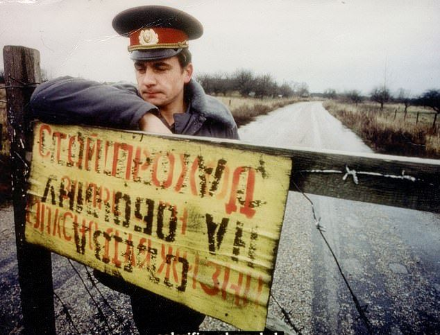 A guard stands by a sign at a closed off road leading to Chernobyl where an explosion occurred on April 26, 1986