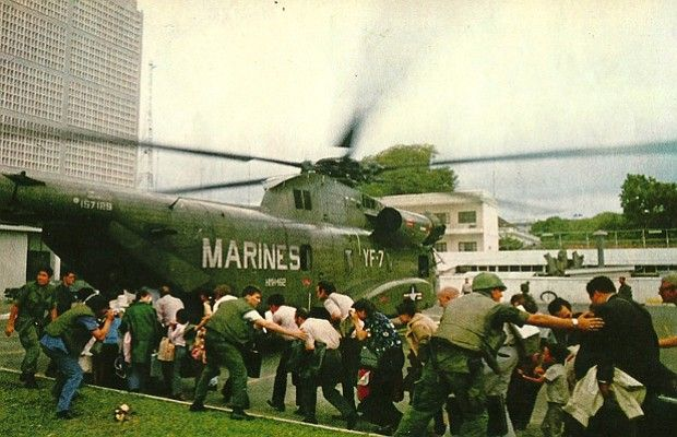 U.S. Marines ushering Vietnamese refugees into helicopter at the U.S. Embassy.